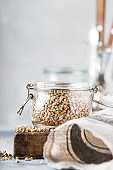 Green buckwheat in glass jar, healthy vegetarian food or raw foods concept, gray kitchen table