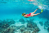 Young woman in snorkeling mask dive underwater with tropical fishes