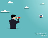 Businessman looking through telescope at to the target