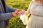 Man putting engagement ring on woman hand. Marriage proposal, wedding
