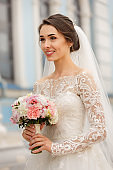 Photography of happy bride in white wedding dress with long sleeves. Bride with beautiful wedding bouquet