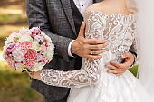 Wedding bouquet with pink and white flowers. Groom in grey suit embrace bride in wedding dress with lons sleeves. Luxury wedding photography