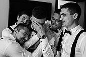 Happy groom and joyful groomsmen embracing after wedding ceremony. Black and white wedding photography