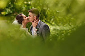 Wedding kiss. Bride and groom kisses on green background