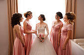 Bride in white wedding dress with long sleeves and bridesmaids in pink dress posing before wedding ceremony