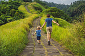 Dad and son tourists in Campuhan Ridge Walk , Scenic Green Valley in Ubud Bali. Traveling with children concept