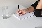 Business concept, notebook, pen and glass of water on the table. Business woman makes a note in a notebook
