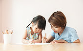 Happy Asian Mother and daughter drawing together.