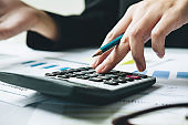 Close up hand of bookkeeper or financial inspector hands making report, calculating or checking balance. Home finances, investment, economy, saving money or insurance concept