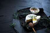 Сamembert cheese with rosemary and honey on black slate background.Italian, French cheese.Brie type of cheese.