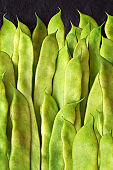 Green flat beans in pods lie on a stone slab. View from above,