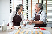 senior couple baking cookies.