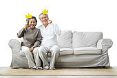 Senior Couple holding yellow paper crowns on stick.