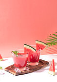 Fresh water melon juice and watermelon slice on red background. summer drink.