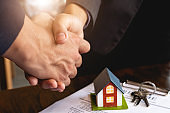 Real estate broker and customer shaking hands after signing a contract - Real estate, home loan and insurance concept