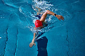 Female athlete swimming fast in crawl style.  Splashes of water scatter in different directions.