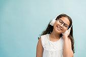 Female Child With Long Brown Hair Enjoying Music