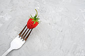 Red ripe strawberry on fork on background of gray stone table with copy space. Concept diet food or vegetarianism. Minimal style Top view