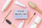 Light box text Good morning and set of cosmetics products and tools for shower or bath on pink background. Concept female morning body care, face, teeth for beauty and health. Template Top view