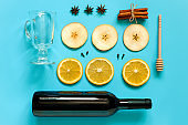 Mulled Wine Ingredients, still life on blue background. Bottle of wine, cinnamon sticks, slices of orange, apple, anise and mug. Concept culinary recipe Creative Top view Flat lay