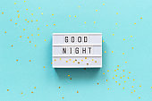 Lightbox text Good Night and gold star on blue paper background. Concept Sweet dreams Greeting card Top view Creative flat lay