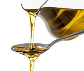 Pouring of olive oil from glass jug into spoon on white background