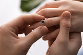 Young man putting engagement ring on fiancee's finger, closeup