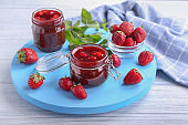 Glass jars with delicious strawberry jam on board