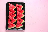 Plate with slices of ripe watermelon on color background