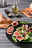 Plates with delicious fig salad on wooden table