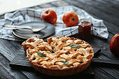 Wooden board with tasty homemade apple pie on table