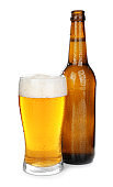 Glass and bottle of cold beer on white background