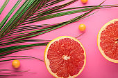 Slices of ripe juicy grapefruit and palm leaf on color background