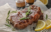 Tasty grilled steak with rosemary and lemon on parchment