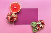 Flat lay composition with various delicious fruits and sheet of paper on color background