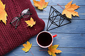 Composition with cup of delicious mulled wine, warm sweater and autumn leaves on color wooden background