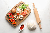 Composition with raw dough and ingredients for pizza on light background