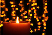Burning candle against blurred lights