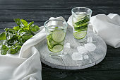 Glasses of fresh cucumber water on wooden board
