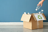 Young woman throwing plastic bottle into cardboard box indoors. Recycling concept