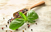 Fresh basil and scoop with spices on wooden background