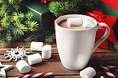 Cup of hot cocoa with marshmallows and Christmas decorations on wooden table