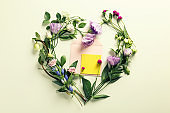 Flat lay composition with flowers and envelope on light background