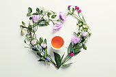 Flat lay composition with beautiful flowers and cup of tea on white background