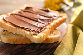Toasted bread with chocolate paste on wooden board, closeup