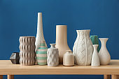 Different vases on table against color background