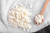 Tasty cottage cheese with wooden spoon on table