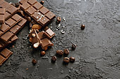 Tasty chocolate with coffee beans on grey background