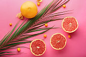 Ripe juicy grapefruits and palm leaf on color background, flat lay