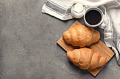 Board with tasty croissants and cup of coffee on grey background